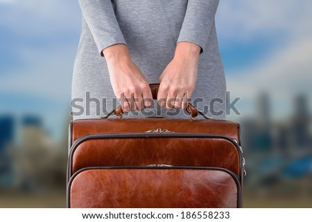 Woman holds leather suitcase in hands against blurred city background - stock photo