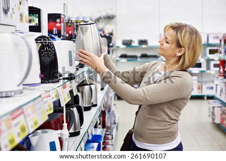 Woman housewife shopping for electric kettle, smiling - stock photo