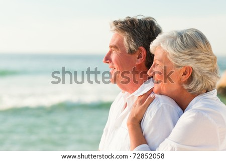 Woman hugging her husband at the beach - stock photo