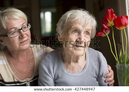 Woman hugging her old mother. - stock photo