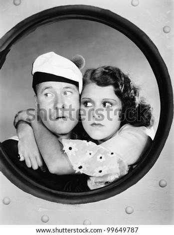 Woman hugging sailor at porthole - stock photo