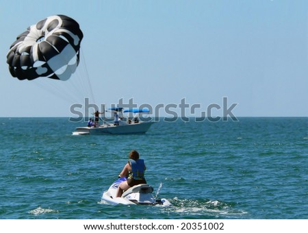 Woman idling on a jet ski in calm water watching para-sailing in the distance. Horizon is placed just below center. Parachute is black and white. It is a sunny day with no clouds in the blue sky - stock photo