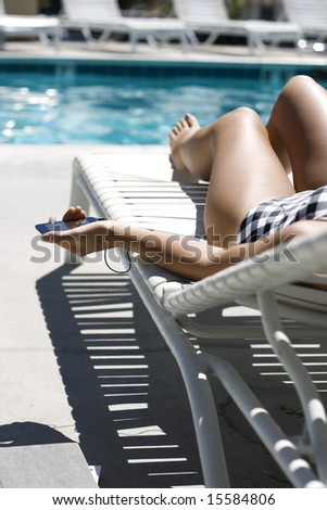 Woman in a bathing-suit laying by the pool, listening to music. - stock photo