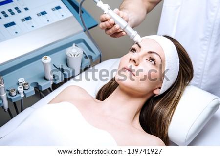 woman in a beauty clinic by becoming a facial - stock photo