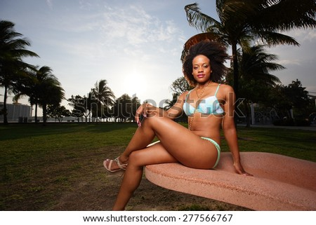 Woman in a bikini sitting with legs crossed stock image - stock photo