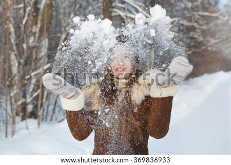 woman in a black cap throwing snowball. Flying Snowflakes. Sunny day. Joyful Beauty young woman Having Fun in Winter Park.  - stock photo