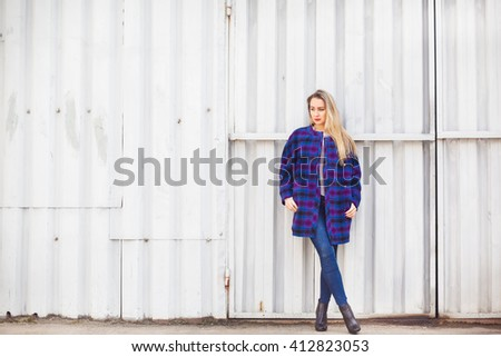 Woman  in a blue coat stands on the background of old wall - stock photo