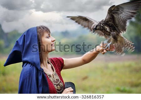 woman in a blue hooded cloak holding a falcon on his arm - stock photo