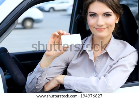 Woman in a car shows a blank card with a place for your message - stock photo