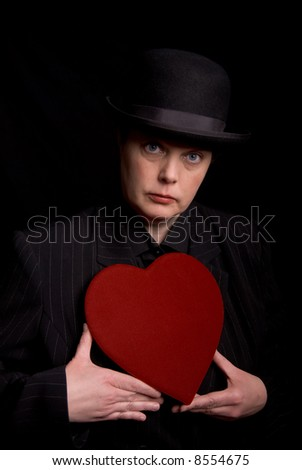 Woman in a derby and suit holding a red candy heart box - stock photo