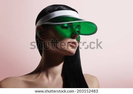 woman in a green sun visor on a pinky background  - stock photo