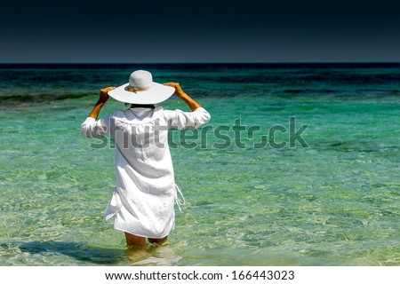 woman in a hat at the beach - stock photo
