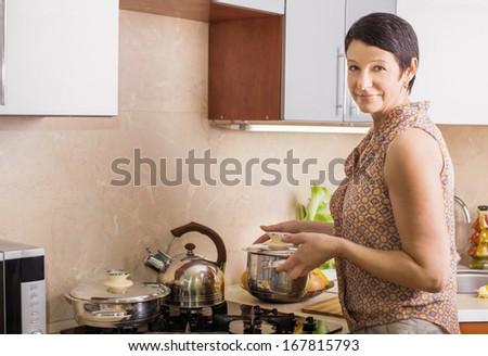 woman in a kitchen is holding a casserole - stock photo