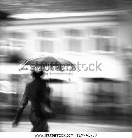 Woman in a rain walking with umbrella. Unrecognizable person in motion blur. - stock photo