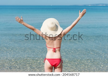 Woman in a red bikini celebrating her vacation at the sea standing on a tropical beach looking out over the ocean with a wide brimmed straw sunhat on her head and her arms opened wide - stock photo