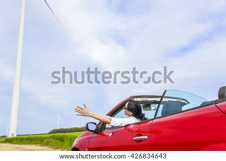 Woman in a red cabriolet car in a field with wind power, raises her arms up. Travel or freedom concept. - stock photo