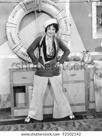 Woman in a sailors outfit in front of a life preserver - stock photo