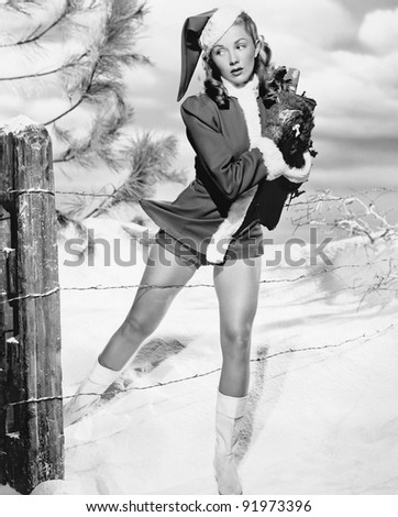 Woman in a Santa costume getting caught on a barbed wire fence - stock photo