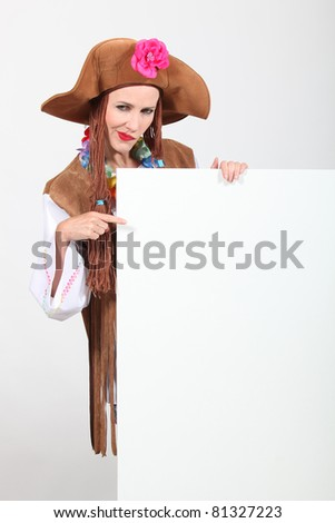 Woman in a seventies hippy costume pointing at a board left blank for your message - stock photo