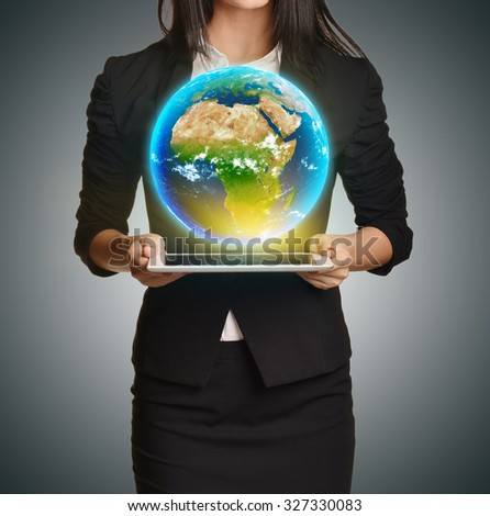 Woman in a suit holding tablet palms and Earth upon him. Elements of this image are furnished by NASA - stock photo