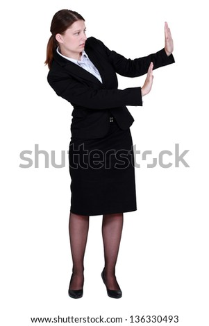 woman in a suit trying to protect herself with her hands - stock photo