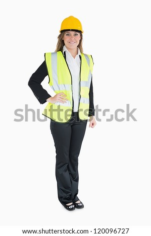 Woman in a suit wearing high visibility vest and hard hat - stock photo
