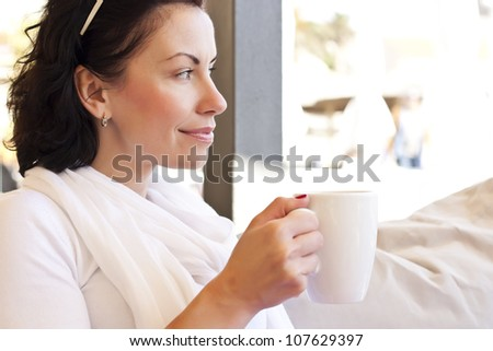 Woman in a summer restaurant drinking coffee - stock photo