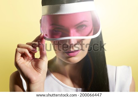 woman in a sun visor on a sunny yellow background - stock photo
