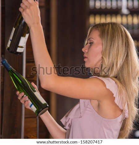 Woman in a supermarket comparing two wines - white and red - stock photo