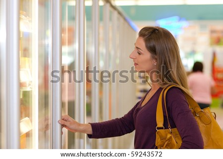 Woman in a supermarket standing in front of the freezer looking for her favorite frozen food - stock photo