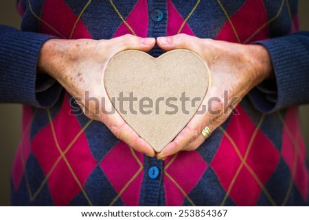 woman in a sweater compressing a paper heart between her hands with a drama filter (shallow depth of field) - stock photo