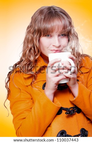 Woman in a warm winter coat sipping and savouring a mug of hot steaming coffee or soup which she is nurturing in cupped hands in a wintertime warm up conceptual - stock photo