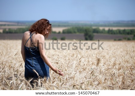 Woman in a wheat field on a summer day - stock photo