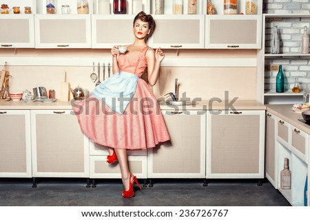 Woman in an apron in the kitchen drinking from a cup and waving. - stock photo