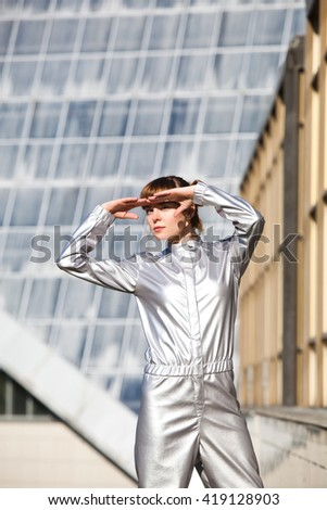 Woman in astronaut costume standing on the grass and watching away - stock photo
