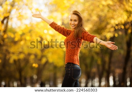Woman in autumn. Beautiful happy young woman in the fall park. Joyful woman having fun outdoors in a bright yellow trees. Colorful fall concept. - stock photo