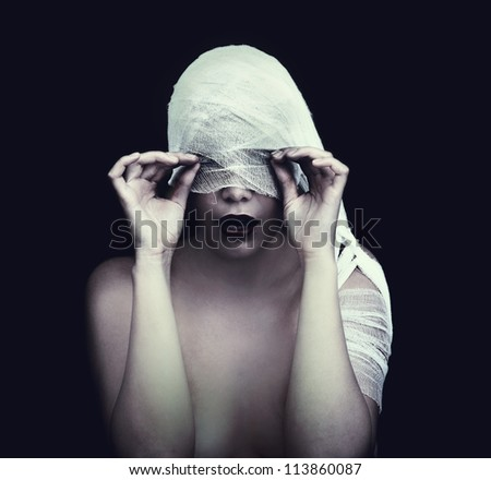 woman in bandage over black background (gothic style concept) - stock photo