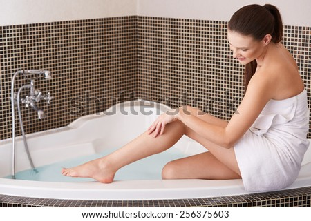 Woman in Bathroom Cares About Her Perfect Legs - stock photo