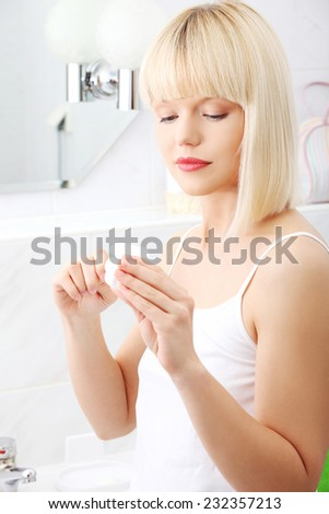 Woman in bathroom with dental floss. - stock photo