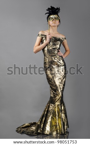 Woman in beautiful golden dress with mask - stock photo