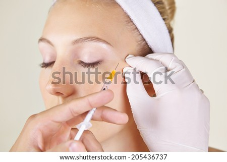 Woman in beauty clinic getting wrinkles treatment near her ayes ageinst crow's feet - stock photo