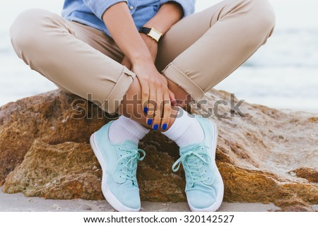Woman in beige pants and a denim shirt and turquoise sneakers sitting on a rock by the sea. Shirt sleeves rolled up, watch on his arm, a blue manicure. Arms and legs crossed. Close-up, outdoors. - stock photo