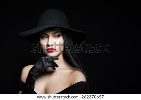 Woman in big black hat, studio portrait, dark background - stock photo