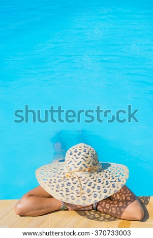 woman in big hat relaxing on the swimming pool - stock photo