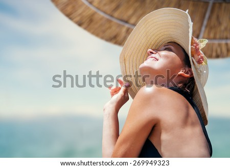 Woman in big straw hat enjoyed with summer sun - stock photo