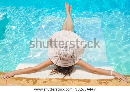 Woman in big whire hat relaxing on the swimming pool. Girl at travel spa resort pool. Summer luxury vacation. - stock photo