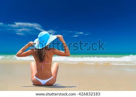 Woman in bikini and hat at tropical beach - stock photo