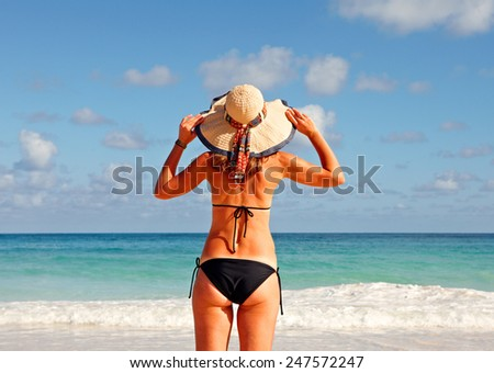Woman in bikini and hat on tropical beach - stock photo