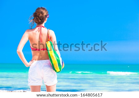 Woman in bikini and sunglasses with beach bag - stock photo