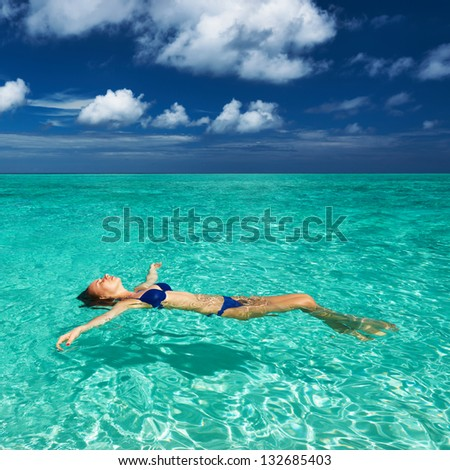 Woman in bikini lying on water at tropical beach - stock photo